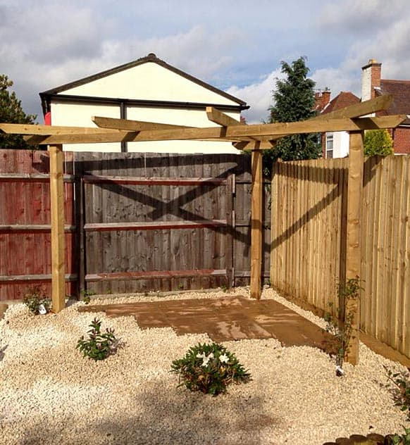 Wooden pergola situated in the corner of a garden