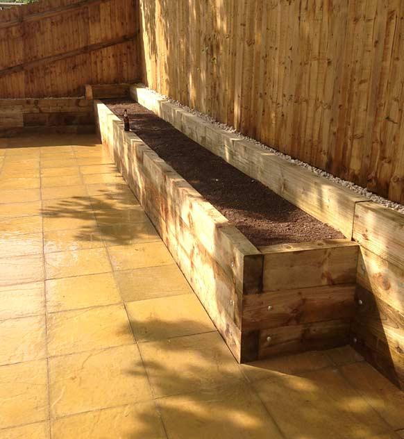 Wooden sleepers raised flower bed